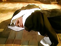 Michelle Thorne lying on the ground in a nun's outfit as she slides her hand underneath and starts rubbing herself before flipping over and opening her clothes to reveal her fully nude body including explicit shots in between her legs while she continues