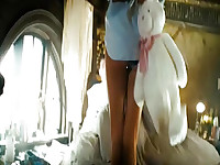 Rosie Huntington-Whiteley walking up a stairway in a pair of panties and a button-down shirt that only comes partway down her butt, giving us a good look as the camera follows her up to a guy's bed. There she hands him a stuffed rabbit and straddles him,