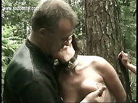 Horny slave tied to tree gets pulled on her beautiful tits and gets hit on her cunt with a stick and hands