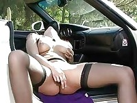 Busty redhead in stockings plays with sex toy in car