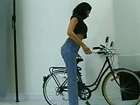 Sexy brunette rides bike and then goes inside to fuck doggy style