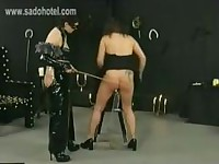 Mistress in latex dress spanks beautiful slave on the ass and on her tied up big tits