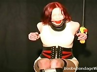 Redhead woman gagged and tied up to a chair in bondage video
