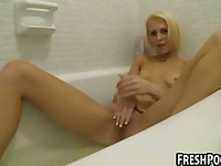 Hot blonde babe plays with her pussy in the bathtub